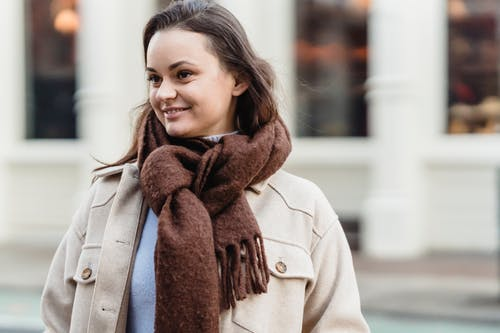 Delighted young lady with long brown hair in stylish outfit and scarf smiling on city street and looking away