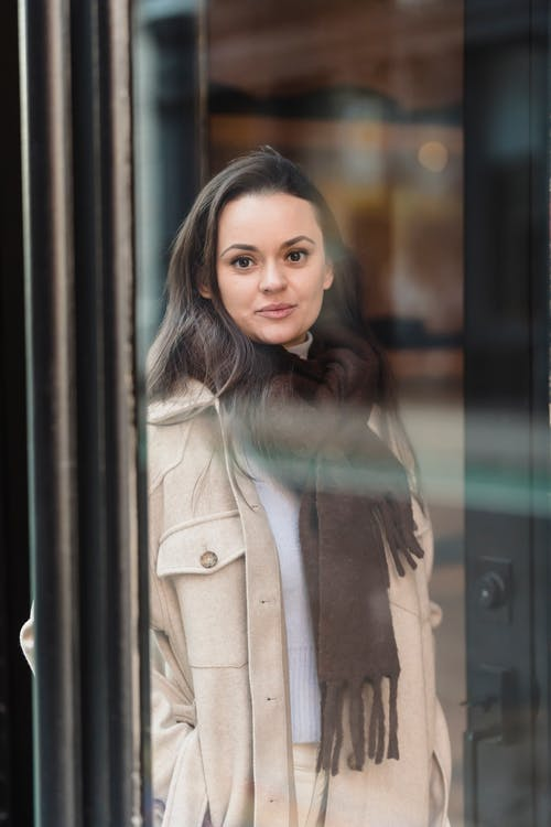 Smiling young woman standing on street and looking at camera through glass door
