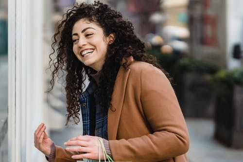 Cheerful young ethnic female with long curly hair in stylish clothes laughing while standing on city street during weekend