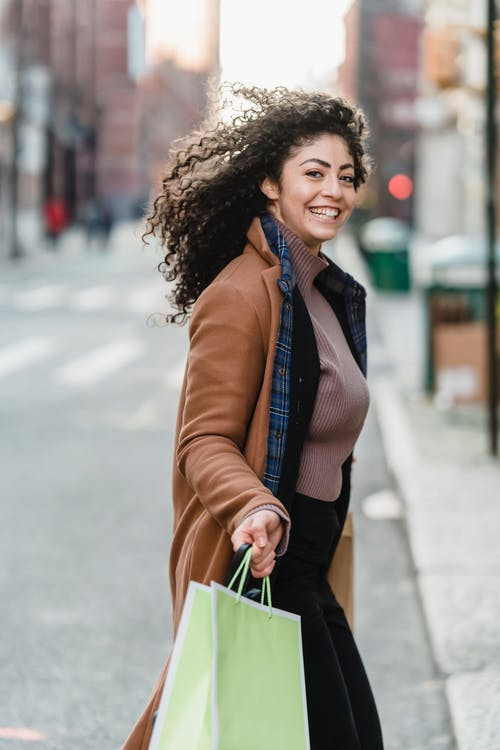 Side view of cheerful ethnic young female shopper with flying curly hair carrying paper shopping bags running on city road