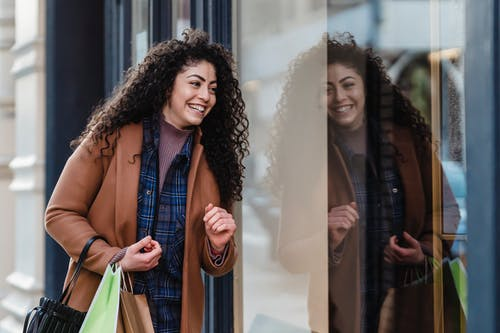 Laughing ethnic female in coat and casual clothes standing with paper bags near showcase after shopping