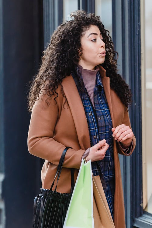 Surprised ethnic female shopper with paper shopping bags looking away with interest standing near showcase on city street