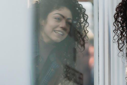 Reflection of smiling ethnic female on street