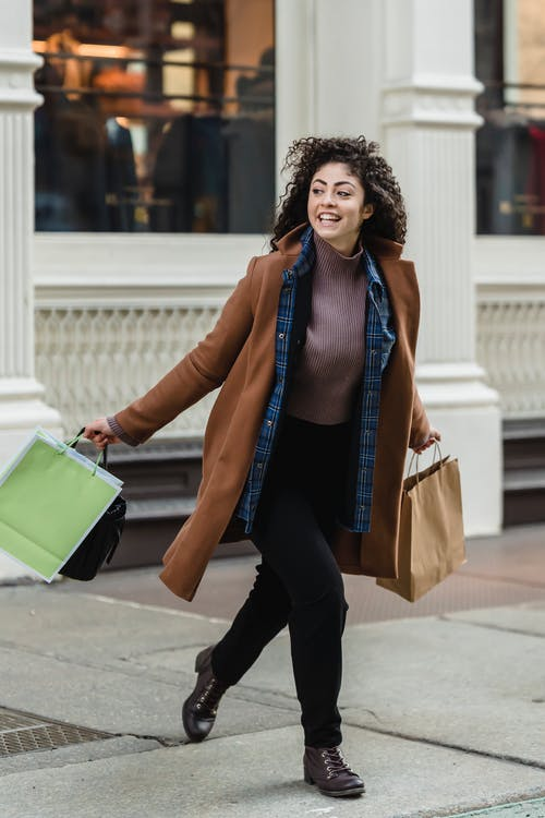 Full body of young smiling ethnic woman in hurry wearing stylish clothes running with purchases in paper bags and looking away