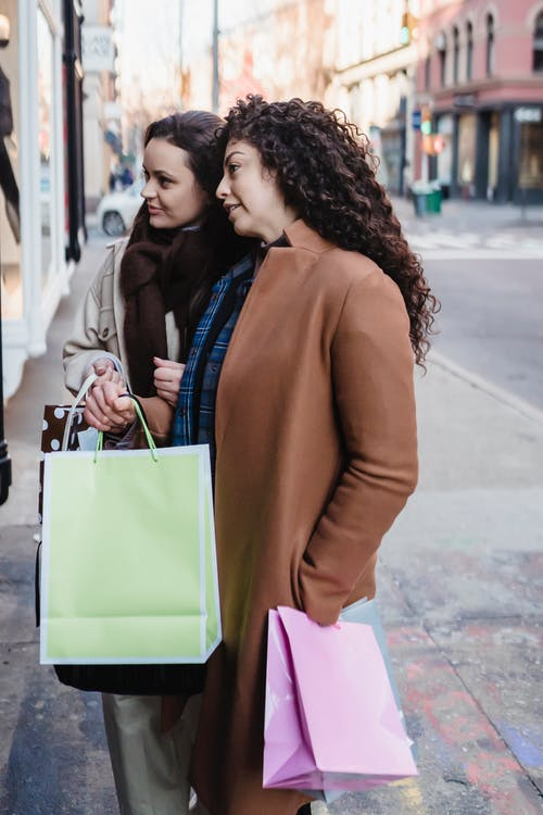Female friend with gift bags talking on street near showcase