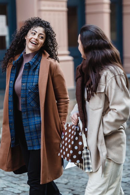Glad ethnic female wearing coat walking near friend carrying gift bag on paved city street