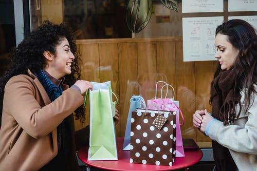 Happy ethnic woman getting present from girlfriend