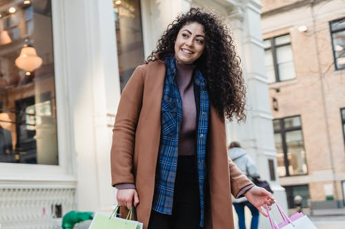 Low angle of positive ethnic female in coat above casual wear standing with bright gift bags on sidewalk and looking away