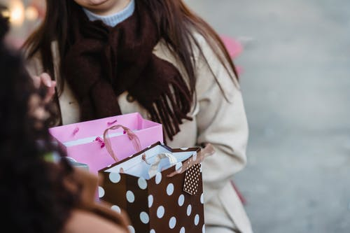 Female friends sitting at table with gift bags