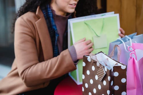 High angle of crop female in coat sitting at table with colorful gift bags placed on table