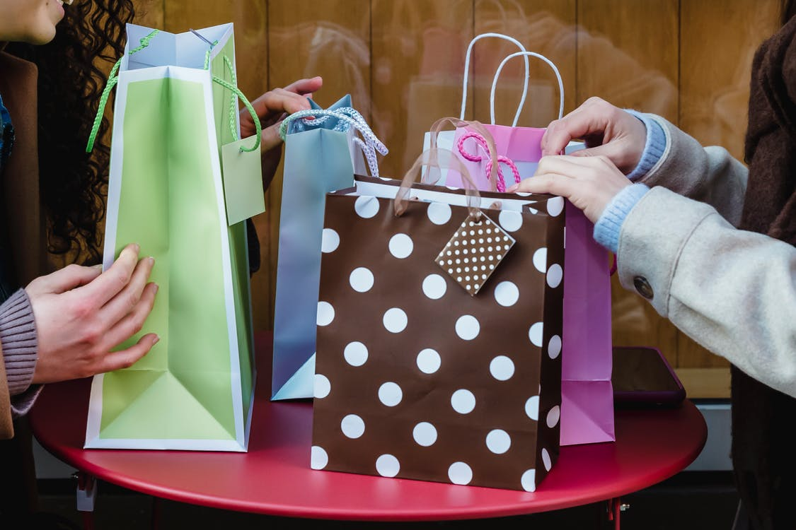 Side view of crop anonymous female friends sitting at table with various colorful gift bags bought for occasion