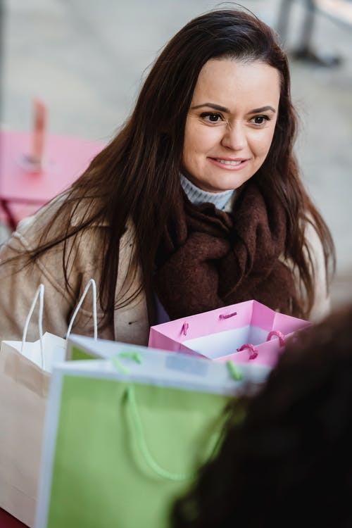 High angle of smiling woman talking to crop girlfriend sitting at table with purchases in present bags