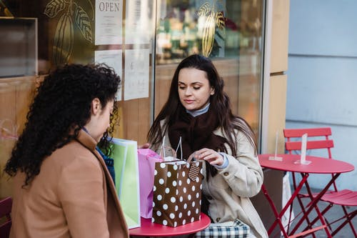 Women looking through purchases in gift bags