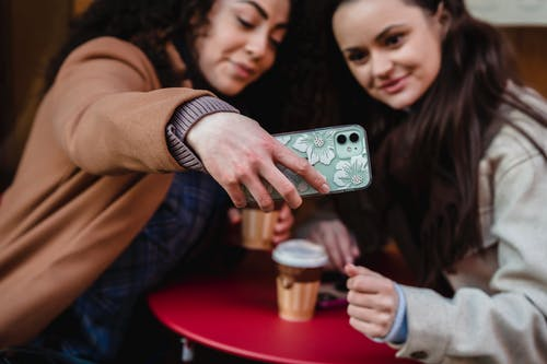 Positive multiracial female friends taking self portrait on smartphone while sitting at table with takeaway coffee on street in city
