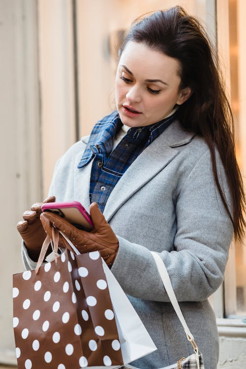 Serious woman browsing smartphone on street