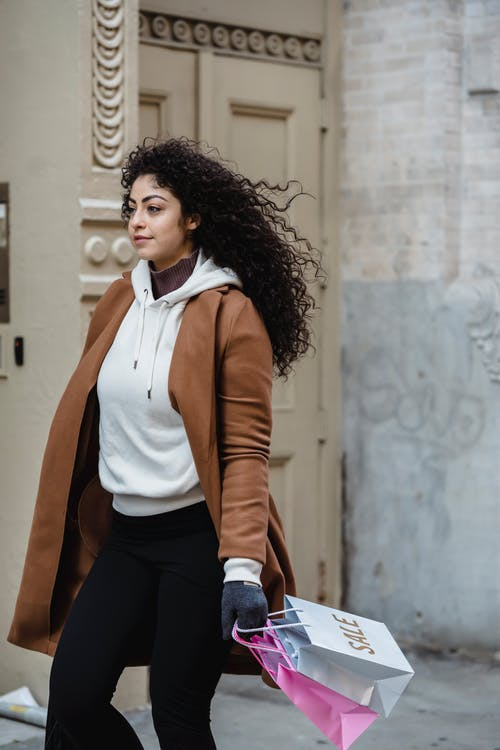 Side view of content ethnic female with curly hair and gift bags strolling on street near aged building in city