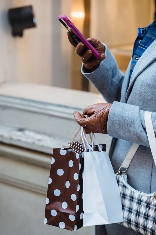 Unrecognizable female wearing warm clothes with gift bags texting message on cellphone while standing near window of building in city
