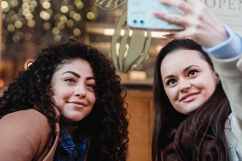 Happy multiethnic women taking selfie in city