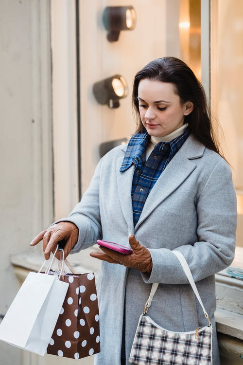 Stylish woman with shopping bags browsing smartphone
