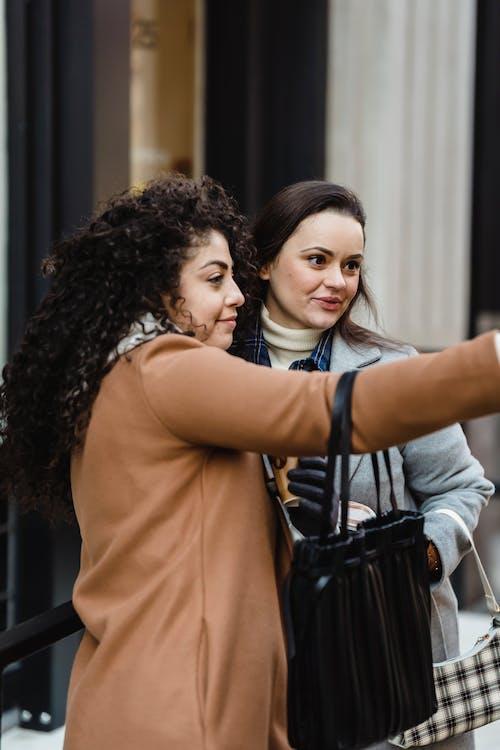 Cheerful diverse women taking selfie near building