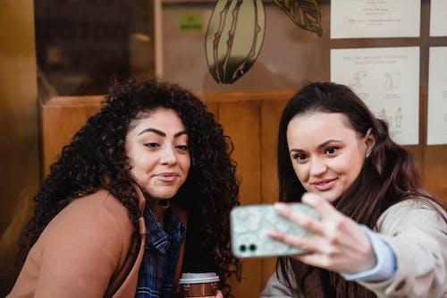 Smiling multiracial women taking selfie near building