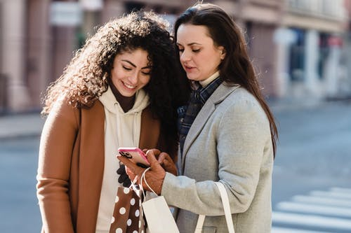 Girlfriends in city street checking information on smartphone