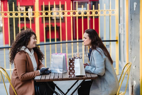 Side view of young female friends wearing warm coats while sitting at table in chairs and having conversation in street near gift packages and yellow fence in town in daylight