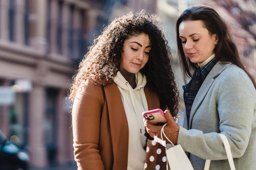 Young girlfriends in warm coats and gloves standing in street with gift packages while looking at information on cellphone near buildings in town in sunny day