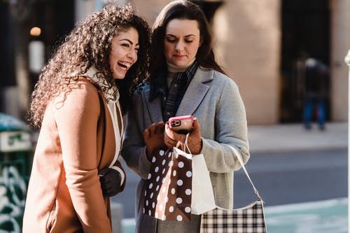 Girlfriends using smartphone in city street