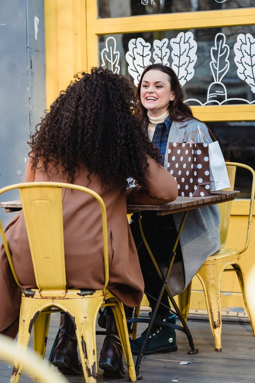 Positive young female friends in warm coats having conversation in street while sitting at table with gift packages in chairs near yellow building in town in daylight