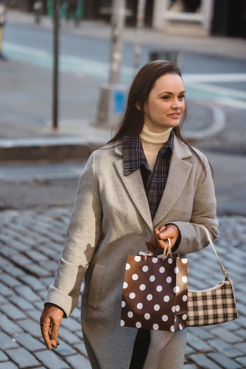 Positive young woman wearing warm coat and gloves strolling in street with gift packages and purse near road in town while looking away in sunny day