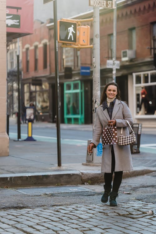 Smiling woman with gift package and purse strolling in street