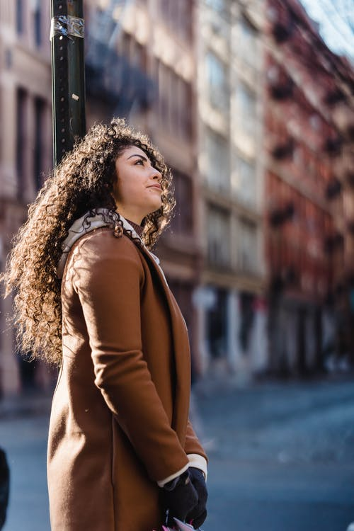 Side view of young woman wearing warm coat while standing in street near road and building in town in sunny day
