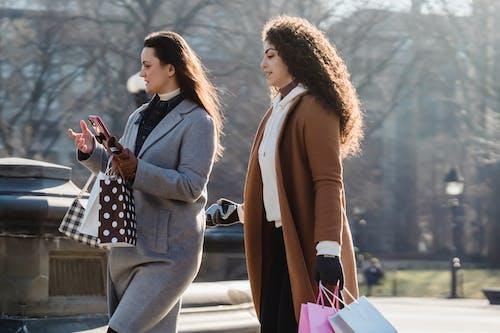 Young women in outerwear walking on city street