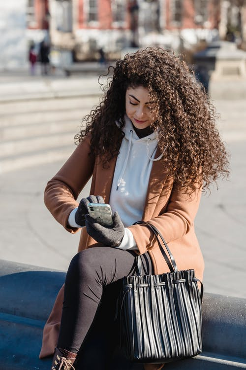 Young woman using smartphone on street bench