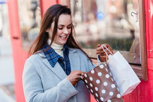 Happy young brunette wearing blue coat looking in shopping bags while standing on city street on sunny spring day