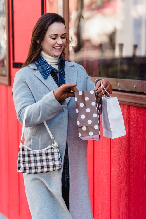 Cheerful young female shopper in warm clothes looking in shopping bags with purchases while strolling on city street