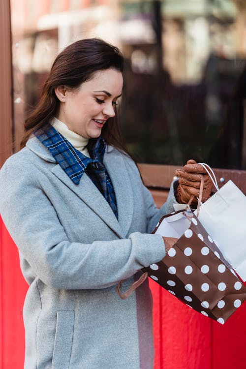 Content woman looking at purchases on bags on street