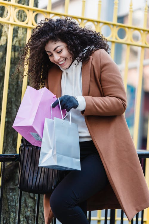Excited woman looking in shopping bags near street fence