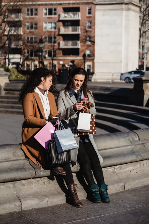 Full body young female friends in warm clothes using smartphone and chatting while sitting on street stairs with shopping bags on sunny spring day