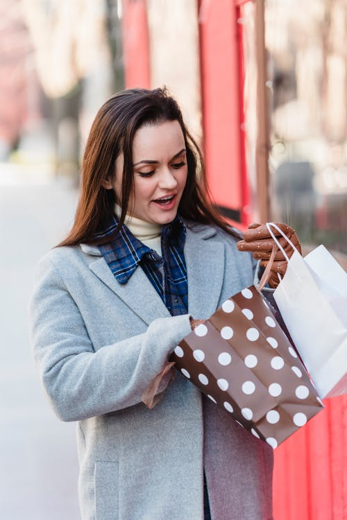 Excited young female wearing blue coat looking in shopping bags while standing on street on sunny cold weather