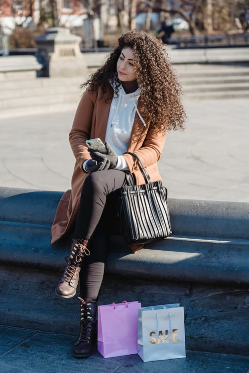 Full body young female wearing warm coat using mobile phone while sitting on street stairs near shopping bags and looking away in thoughts