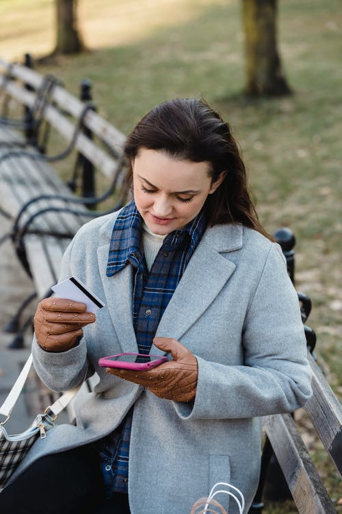 Content young female in blue coat making online payment with smartphone while sitting on bench in park on early spring day