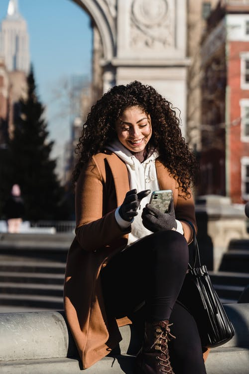 Happy young female with curly hair wearing warm coat and gloves using mobile phone and sitting on street stairs on sunny spring day