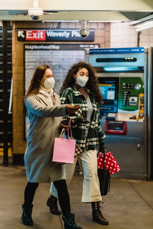 Women friends in protective masks and casual clothes with shopping bags walking in subway hallway during coronavirus
