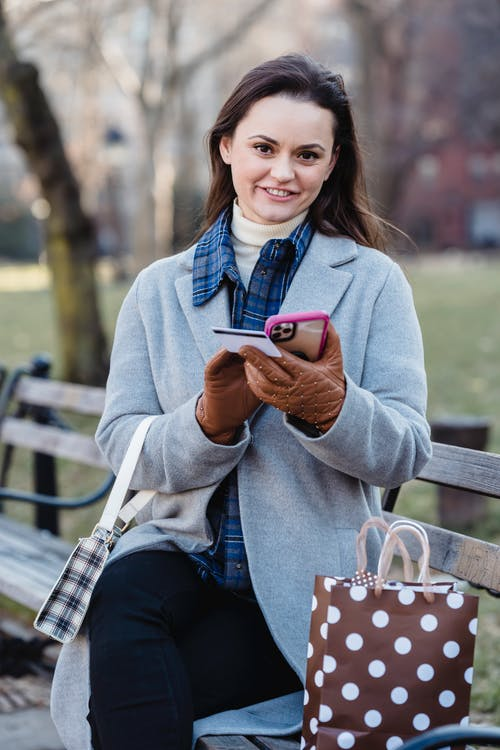 Cheerful woman in casual clothes sitting on wooden bench in park and entering credit card details on smartphone during online shopping in daylight
