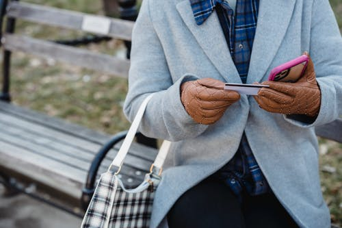 Female sitting on bench and entering credit card detail on smartphone