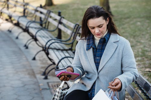 Pensive woman with smartphone and credit card sitting on bench on street