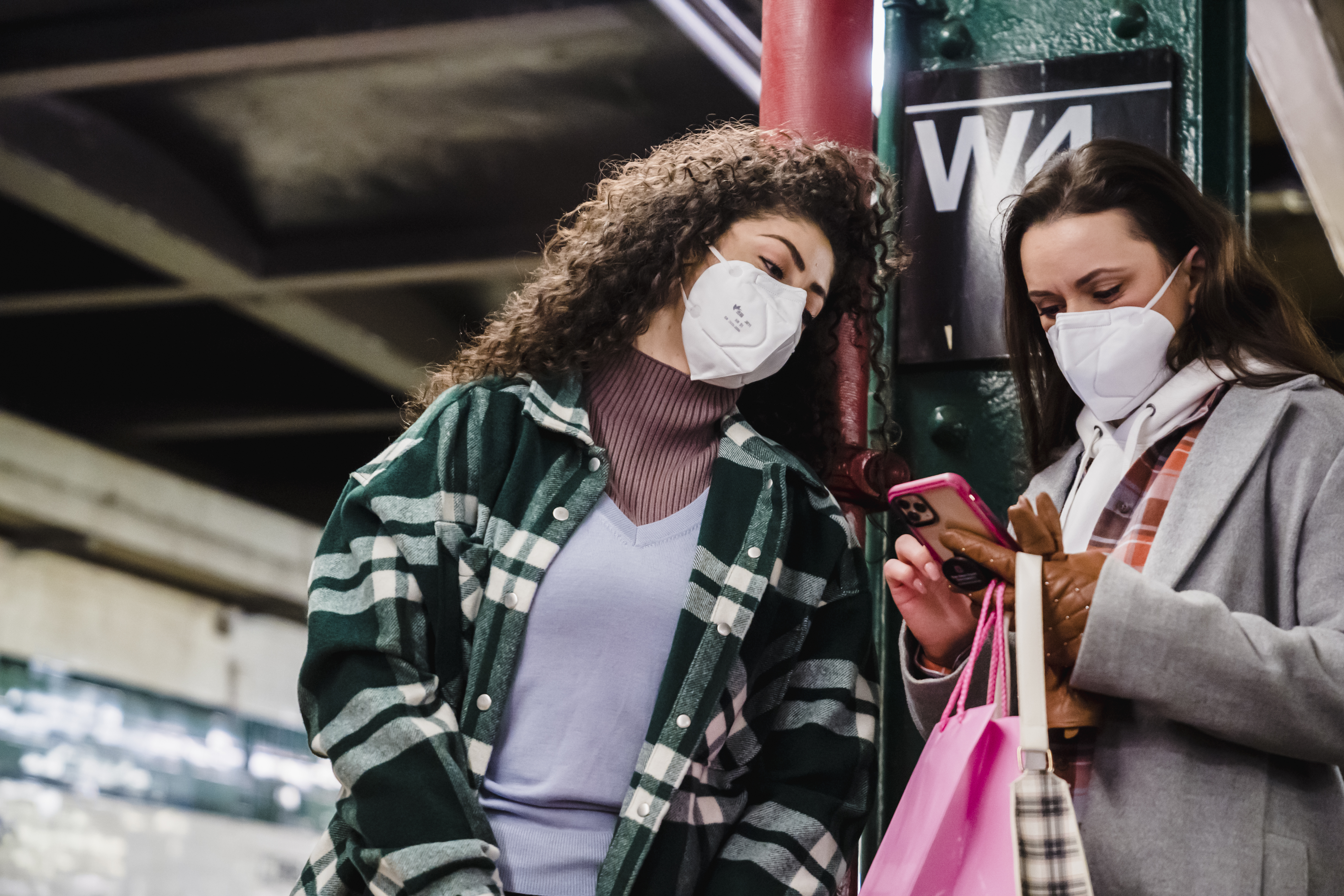 girlfriends in masks using cellphone with paper bag in metro