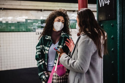 Young female friends in outerwear and protective masks with cellphone and purse with paper bag while standing on light metro station and looking at each other